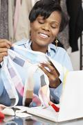 African fashion designer holding fabric swatches Stock Photos