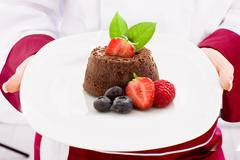 Chef presenting chocolate cake with strawberries Stock Photos