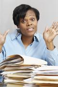 African businesswoman behind stacks of folders Stock Photos