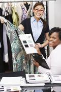 Multi-ethnic fashion designers holding designs and dress Stock Photos