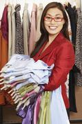 Asian woman holding bunch of clothing Stock Photos