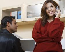 Stock Photo of Hispanic man watching girlfriend talk on telephone
