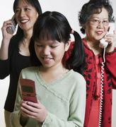 Multi-generational Asian family using telephone, cordless telephone and cell Stock Photos