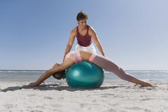 Hispanic trainer assisting woman on exercise ball Stock Photos