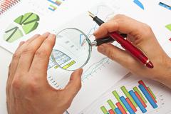 Stock Photo of magnifying glass in hand and paper