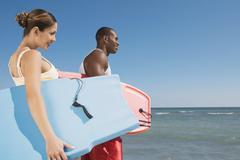 Multi-ethnic couple holding bodyboards - stock photo