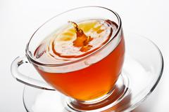tea splash in glass cup - stock photo