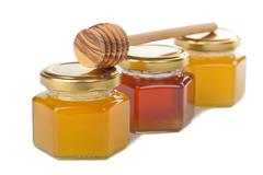 Stock Photo of honey in bottles and wooden dipper isolated