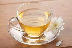 cup of green tea and white flower - stock photo