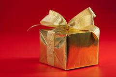 Golden gift box over red background Stock Photos