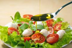 olive oil pouring over salad - stock photo