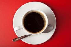 cup of coffee over red background - stock photo