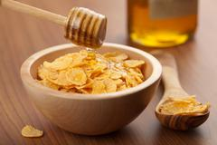 honey pouring over cornflakes - stock photo