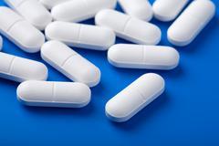 white pills over blue - stock photo