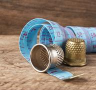 two thimble and measuring tape - stock photo