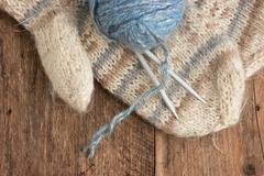 Stock Photo of balls of yarn and mittens on a wooden background