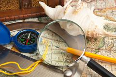magnifying glass and a compass - stock photo