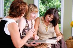 three mature women look at a photo album - stock photo