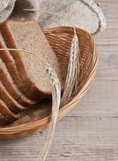 slices of rye bread and ears of corn in basket - stock photo