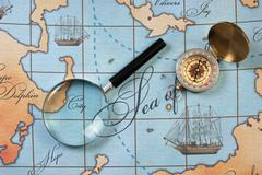 magnifier and compass on  map - stock photo