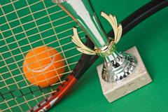 Stock Photo of sports awards and  tennis racquets on  green table