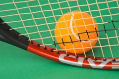 Tennis racket and  ball on green background Stock Photos