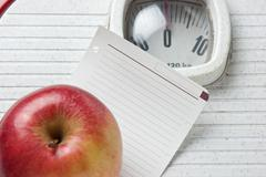Stock Photo of apple and a note on floor scales