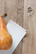 Stock Photo of pear and a note  on a wooden background