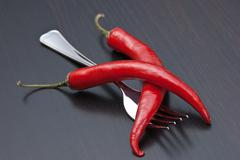 red chili peppers and fork on the kitchen table - stock photo