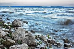 surf on rocky shore - stock photo