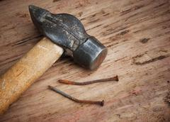old hammer and a rusty nail - stock photo
