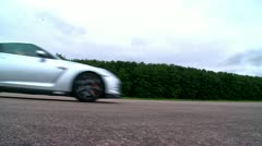 Nissan GTR profile coming to a gentle stop on racetrack Stock Footage
