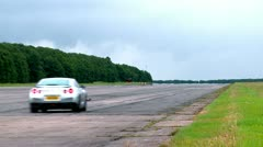 Nissan GRT shooting into distance on racetrack handling track Stock Footage