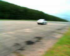 Nissan GTR speeds into distance as camera pans along racing track Stock Footage