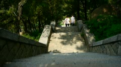 Tourists walking in mountain stone steps,vines wrapped around arch door,Chinese Stock Footage
