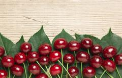 berry cherry with leaves on wooden background - stock photo