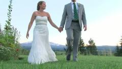 Walking Bride and Groom in Mountain Field Stock Footage