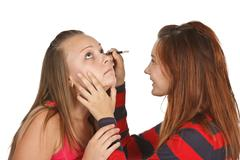 Stock Photo of two teenage girls dye their eyelashes isolated