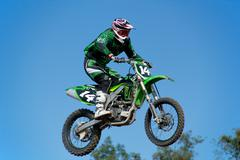 motorcycle jumping against blue sky - stock photo