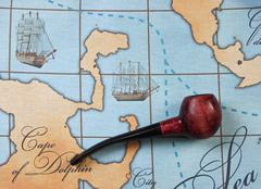 Tobacco pipe on map Stock Photos