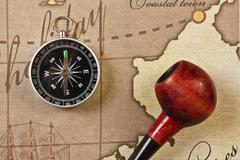 tobacco pipe and compass on map - stock photo