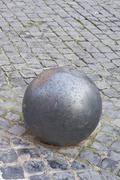 Stock Photo of iron ball on cobblestone
