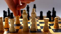 Playing chess closeup, wooden chess board, business concept, grey background Stock Footage