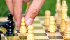 Playing chess closeup, on the grass in the park, wooden chessboard Stock Footage
