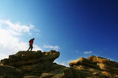 male stand on the rock - stock photo
