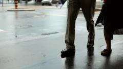 People walking by on wet sidewalk Stock Footage