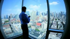Caucasian businessman working on mobile phone in office overlooking Manhattan  - stock footage
