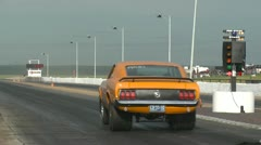 Motorsports, drag racing, orange mustang launch with 1970 period license plate Stock Footage