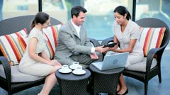 Diverse management team discussing investment banking outdoor on touch screen  - stock footage