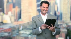 Caucasian manager planning funds on touch screen on rooftop in city  - stock footage